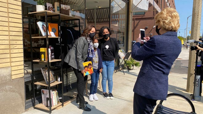 """Michigan Sen. Debbie Stabenow, right, takes a picture of Vice President-elect Kamala Harris posing for a photo on Sept. 22, 2020 with Egypt Otis and her nine-year-old daughter Eva Allen in front of their downtown Flint, Mich., bookstore, the Comma Bookstore & Social Hub. For countless women and girls, Harris' achievement of reaching the second highest office in the country represents hope, validation and the shattering of a proverbial glass ceiling that has kept mostly white men perched at the top tiers of American government. """"My daughter is going to be a part of history because she had the opportunity to have a conversation with our first Black woman vice president,"""" said Otis.  """"It just shows you how important representation is."""""""