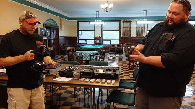 Steve Bartell, left, and Josiah Lee Henson demonstrate some of the electronic equipment they brought along for a night of ghost hunting Friday at the Masonic Temple in Freeport.