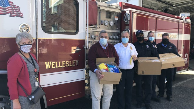 Wellesley Public Schools administrators load up boxes of masks from Wellesley Fire Department headquarters  last month. Pictured, from left: Linda Corridan, WPS director of nursing; Dr. David Lussier, WPS superintendent;  fire chief Rick DeLorie; fIrefighters Gerard Jones and Danielle Fitzpatrick; and Lt. Paul Delaney. The child-sized masks were sewn by members of the group Sewing COVID-19 Help -- Working Together, with supplies purchased from a Wellesley COVID-19 Relief Fund grant that was awarded to the Wellesley Fire Department earlier in the fall.