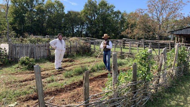 """Chandler Wahrmund and Nathan Giles work the garden on the Barrington Plantation at Washington-on-the-Brazos. They wear period costumes but don't stay """"in character"""" as 19th-century people, more third-person than first-person interpretation."""