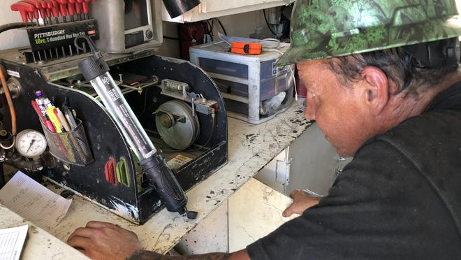 Shawn Epp with Southwind Drilling Inc., Ellinwood, on Wednesday was setting up the drilling rig's geolograph, a mechanical device with a number counter that tells rig hands how deep into the earth the rotary drill has penetrated.
