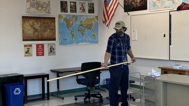 Nick Raso, a member of the Newton Public School Custodian Association's executive board, uses a 6-foot-long piece of wood to demonstrate how close a teacher's desk can be to students' desks inside a Newton North classroom.