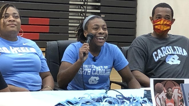 Kayla McPherson, center, laughs as she gives a speech during a signing ceremony at Madison County High School. She's surrounded by her mother, Kashia, left, and father, Nashon.