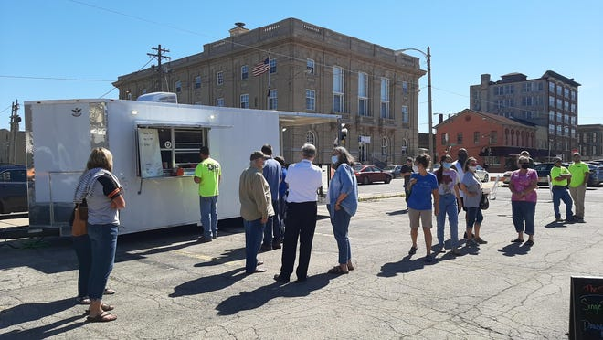 Diners gather for the first-ever Food Truck Frenzy in downtown Freeport during the lunch hour on Friday. The next Food Truck Frenzy will be the first Friday of October.