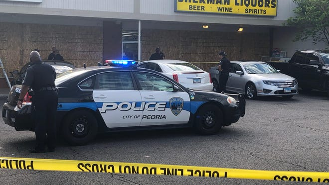 Police investigate the scene of a shooting at Sherman Liquors on Monday night in Peoria.