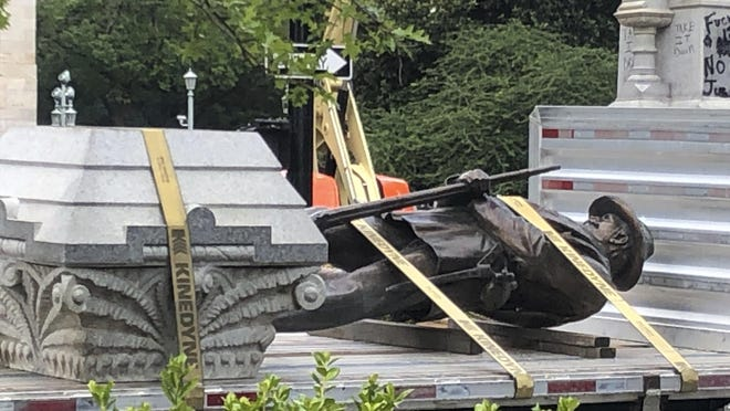 The statue of a Confederate soldier and plinth sit on a flatbed truck at the Old Capitol in Raleigh, N.C., on Sunday, June 21, 2020. After protesters pulled down two smaller statues on the same monument Friday, North Carolina Gov. Roy Cooper ordered the removal of several other monuments to the Confederacy, citing public safety concerns.