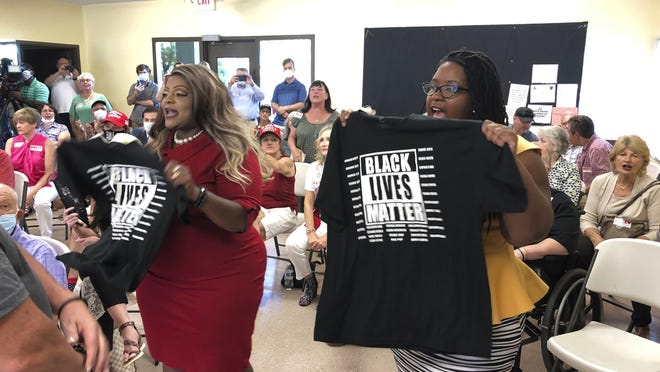 Triana Arnold Gaines (left) and Nselaa Ward hold up Black Lives Matter T-shirts as they protest a speech by U.S. Sen Kelly Loeffler on Thursday, Sept 3, 2020 in Cumming, Georgia. Gaines and Ward kept Loeffler from finishing a campaign speech.