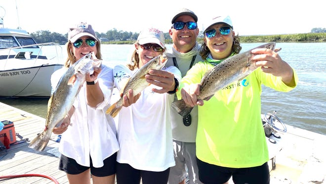 From left to right, with fish, Barbara Smith of Athens, Stacy Horner Carter of Savannah and Dina Posey of Athens were fishing with Capt. Kevin Rose (back) when these and more spotted sea trout were recently landed.