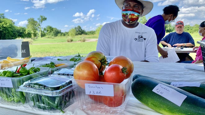 David Faison of Dface Farm in Hephzibah wears a mask and has samples of his produce on display, not to be touched by shoppers, at the Veggie Park Farmers Market on Eve Street on Thursday.