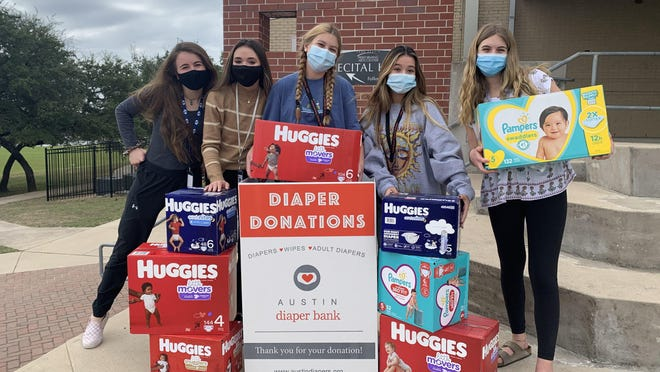 From left to right, Lake Travis High School seniors Savannah Wright and Adelaide Escott, and sophomores Kembree Koleber, Jasmine Leo and Samantha Jansen, hold up some early diaper drive donations. Lake Travis' student council invited Westlake High School to participate in a diaper drive competition the week before the schools' rival football game.
