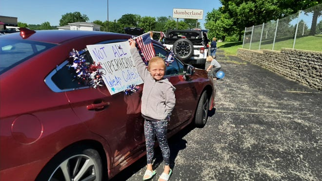 Kara Wilinski of Rockford helps decorate her car with patriotic signs and flags as part of a vehicle cruise Thursday in Freeport organized by Heartland Hospice of Rockford. The cruise traveled to assisted living and nursing facilities to honor local veterans.