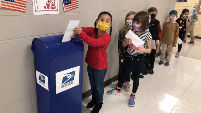 "Lillian William, a second-grader at Logan Elementary School, deposits her ""mail-in"" ballot for the building's mock presidential election Thursday morning in the school's front hallway."