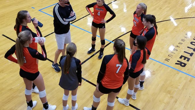 Augusta volleyball coach Brian Hallmark goes over the strategy for his team in their match on Tuesday at Hutter Gymnasium against McPherson. McPherson defeated Augusta 2-0, Augusta defeated El Dorado 2-0 and McPherson defeated El Dorado 2-0.
