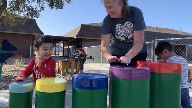 Jean Hertel, a preschool teacher at Early Childhood Connections in Hays, plays on an outdoor drum set with one of her students in the school's playground area. Hertel was recently selected to participate in country musician Jake Gill's Country Music Teacher Classroom Initiative, which helps teachers secure needed school supplies.