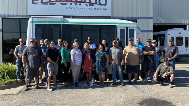 Big Brothers and Big Sisters of Salina workers, along with volunteers from Eldorado, stand Monday morning in front of a bus renovated for BBBS of Salina. Over 40 Eldorado employees put in over 200 hours of volunteer time to help refurbish the bus.