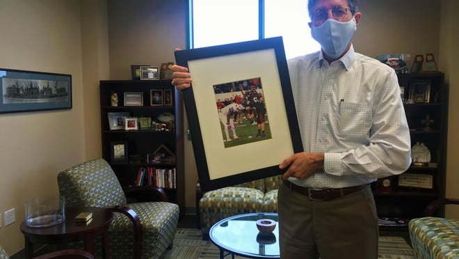 Hanging in Brad Lancaster's office was a copy of the photo the night of state football championship game when Midway High School and Lake Travis High School battled each other for the title. Both representing the district he would leave and join.
