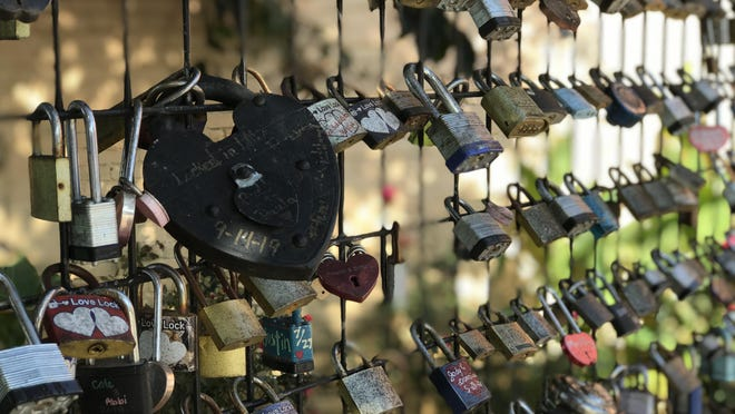 """The Love Lock Fence at the Eiffel Tower Fountain in downtown Paris has become a special place for many since the spring of 2017. As noted by a plaque on the fence, locals and tourists alike are encouraged to """"pick a special lock, add loved ones' names/dates and place the lock on the fence"""" then throw your key into the Eiffel Tower Fountain and forever seal your love in Paris. The first lock was placed on the fence by Miss Arkansas Savannah Skidmore."""
