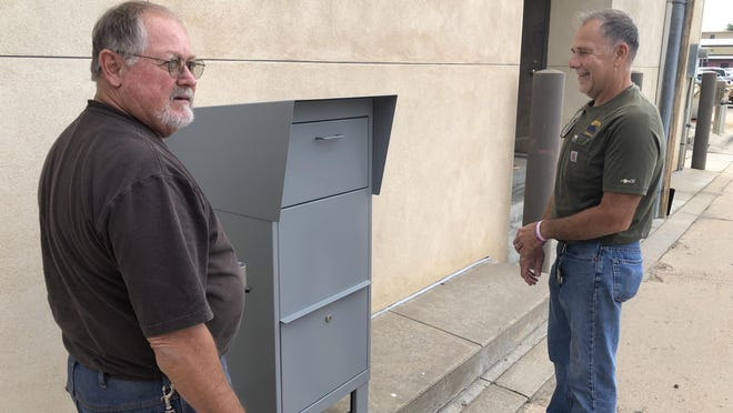 Ron Schumacher, left, and Greg Erbert, both Ellis County maintenance technicians, installed a new drive-up election drop box Friday in the alley south of the Ellis County Administrative Center, 718 Main.