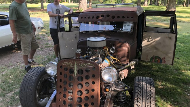 Bradyn Meredith, Hays, visits Saturday about the home-built Rat Rod he and his dad made, with a car enthusiast at the Thunder on the Plains Car Show in Frontier Park East.