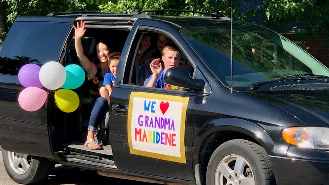 The grandchildren and daughter of Maridene Lundstrom, resident at Bethany Home in Lindsborg, honk and wave from their van on Saturday evening to show their love and support to her and the other residents.