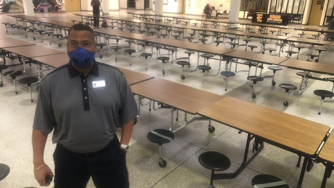 Evans High School Principal Michael Johnson stands in the school's commons area, where cafeteria seating is marked to encourage social distancing.