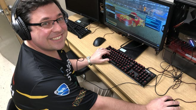 Evans High School esports coach Adam Cowart sits at one of the team's computers equipped to run Rocket League, one of two video games in which the high school competes among high schools across the state.