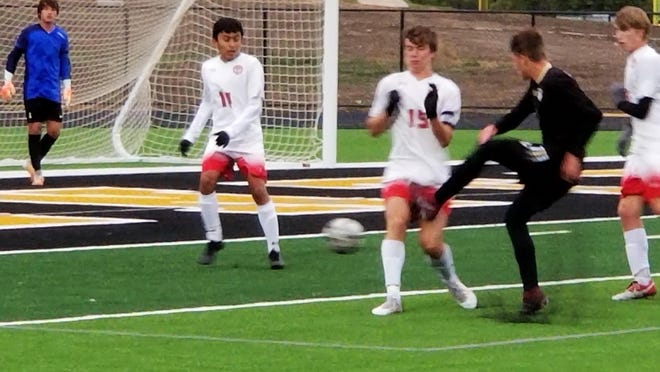Andover Central's Blake Fimreite fires a shot past against Maize's Colby Lampkin with Max Shea of Maize looking on, during the first half of their match on Tuesday, September 8 at Jaguar Stadium. Maize won 2-0.
