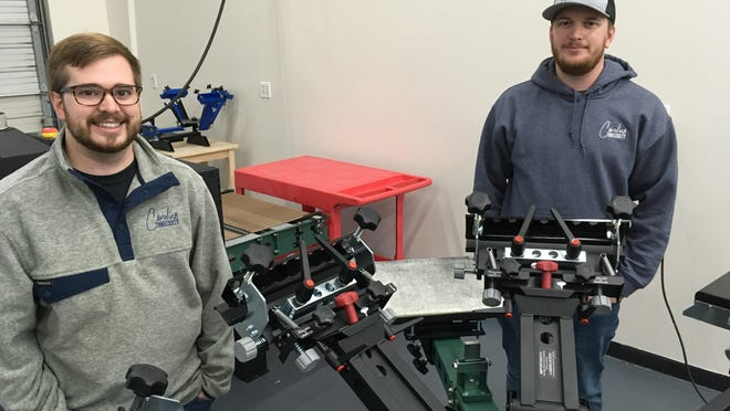 Bryton Mitchell, left, and Cam Mitchell stand by one of the screen printing machines at Carolina Threesixty.