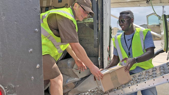 Pilot Julius McPherson, right, of Dallas, who flies the UPS flight from Wichita to Hays every Monday through Saturday, hands packages to Dillon Schmidt, left, of Hays, a UPS air driver.