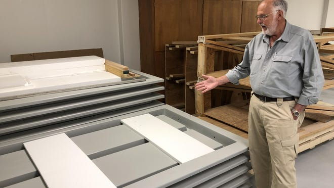 Dave Van Doren, with a stack of Grid-Crete panels, explains how builders construct housing with the reusable plastic molds.