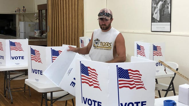 Shane Sulzman, Ellis County Public Works employee, sets up privacy sleeves for voters to use Tuesday when they vote at the Ellis Memorial VFW Post 9139 in Ellis.