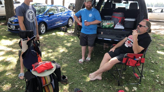 From left to right, Jeremy Walker, Tyler Lett and Cory Day, all from Manhattan, take a break Saturday at noon between 18-hole rounds at the 36th Annual Frontier Open disc golf tournament.