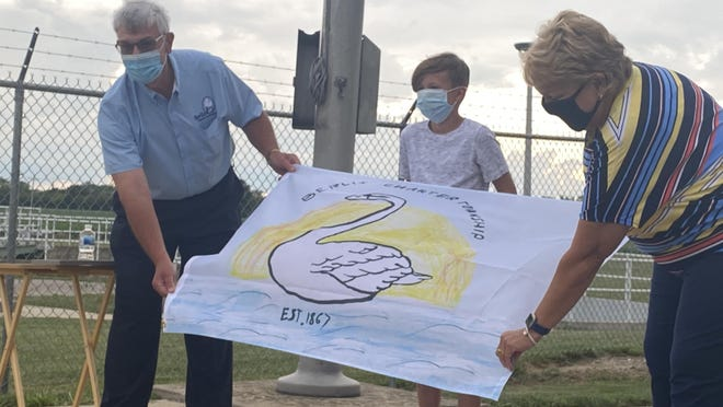 Berlin Township Supervisor Dave Reaume (left) and retiring North Elementary School Principal Millie Grow (right) help incoming fifth-grader Sawyer Schaffer reveal the township's new flag, which features his design. The flag was raised during the township's meeting Monday night.