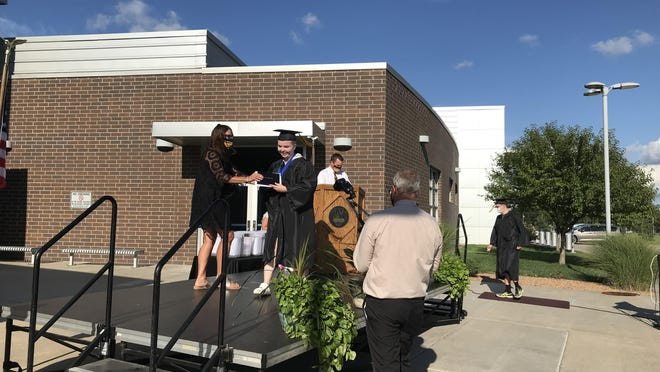 Kayla Anderson receives her diploma during a drive-by graduation ceremony at Newton High School.