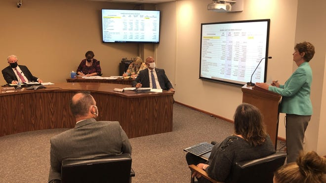 Shawnee County administrative services director Betty Greiner, at the lectern on the right, speaks to county commissioners as they discuss budget matters.