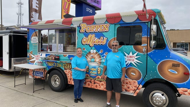 Sharon and Richard Fergison stand in front of their Poppin Minis food truck. Because many events have been canceled this year, the couple has shifted their business model and started setting up at different locations around town.
