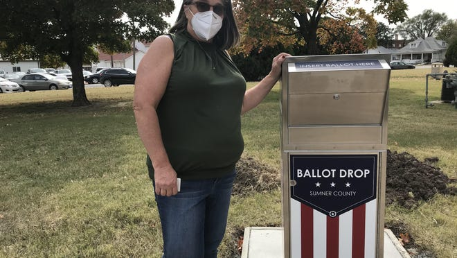 Sumner County Clerk/Elections Officer Debra Norris stands beside a ballot drop box outside the Sumner County Courthouse.