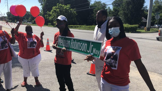 Melquan Robinson Sr. and Chinnika Jackson hold a street sign in honor of their son, Melquan Robinson Jr., on Monday, July 27, 2020.