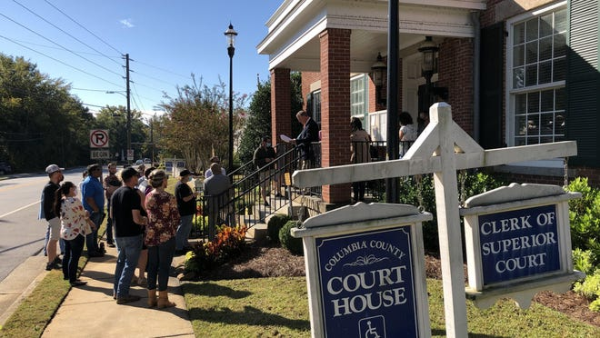Attorney Mark Cleary, shown standing at the head of the stairs, conducted foreclosure proceedings on the former Jones Creek golf course Tuesday, at the Columbia County Courthouse in Appling.