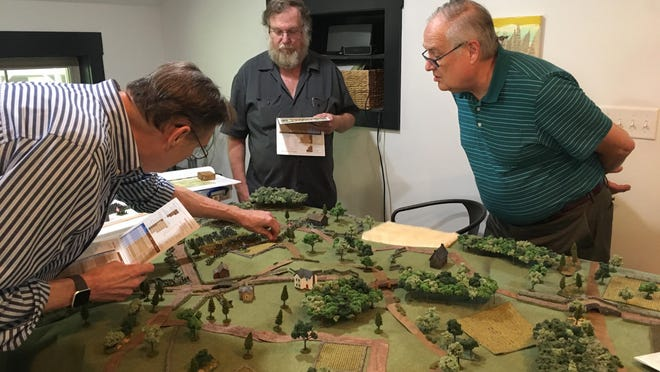 """War gaming enthusiasts Mark Cramer (left) and Mike Pfanenstiel (center) enact the Battle of Bull Run in Cramer's Asheville home for writer David Sullivan (right). Sullivan used the results of the war game to help plot his new novel, titled """"Audacious."""""""