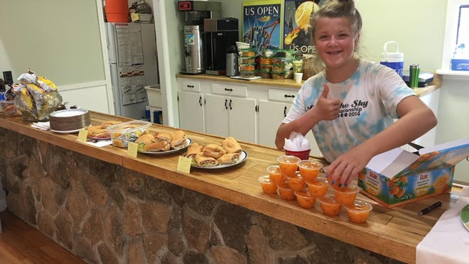 Hendersonville High varsity girls tennis player Lindsay Bull, who helps at Hendersonville Racquet Club, gets snacks ready at a previous summer camp.