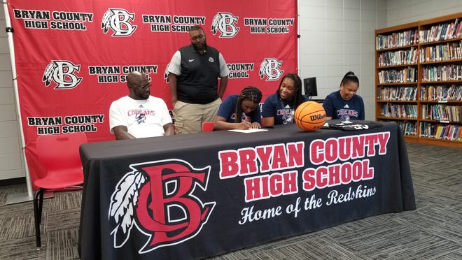 From left: Olonna Rawls' father Oliver Rawls, Olonna Rawls, her mother Tonya McKinney, and her grandmother Kim Jackson, with Bryan County High School basketball coach Mario Mincey (standing) on June 18 as Olonna Rawls signs with Columbus State University.
