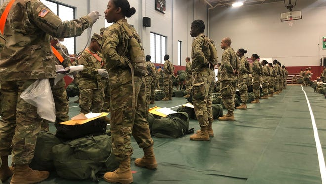 In this image provided by the U.S. Army, recent Army basic combat training graduates have their temperatures taken as they arrive at Fort Lee, Va, on March 31, 2020, after being transported using sterilized buses from Fort Jackson, S.C. COVID-19 has had a dramatic impact on military recruiting, shuttering enlistment stations around the country and forcing thousands of recruiters to woo potential soldiers online. Recruiters have had to abandon their normal visits to high schools and malls, and instead rely almost exclusively on social media to reach young people.
