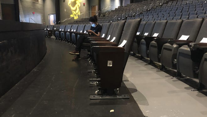 A graduate assistant sits in an empty auditorium during an online lecture on the first day of classes Monday, August 17, 2020, at Georgia Tech in Atlanta. More of Georgia's public universities are opening for the fall term, trying to balance concern about COVID-19 infections against a mandate for on-campus classes citing financial needs and student desires