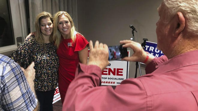 Supporters take photos with construction executive Marjorie Taylor Greene, background right, late Tuesday, Aug. 11, 2020, in Rome, Ga. Greene, criticized for promoting racist videos and adamantly supporting the far-right QAnon conspiracy theory, won the GOP nomination for northwest Georgia's 14th Congressional District.
