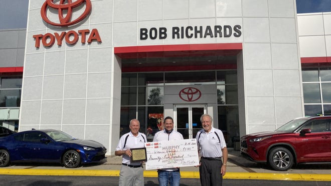 Kent Rowder (from left), Michael Murphy and Jack Morrison pose with a check for the Wounded Warrior organization at Murphy Auto Group's Bob Richards Toyota dealership.