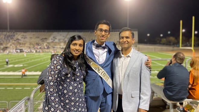 Senior Sohan Agnihotri poses with his parents after being nominated for Westwood High School royalty during halftime of the Warriors' Nov. 20 football game.
