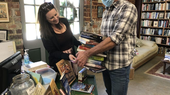 Christine and Jim Dawson sort through their book selections at the checkout. They were in town visiting from Chicago.
