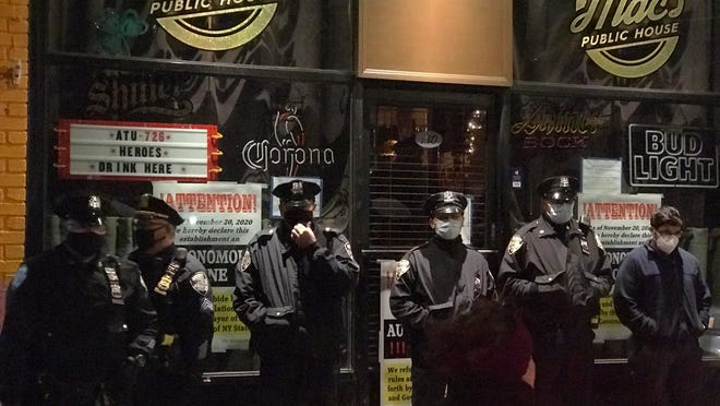 Officers from the New York City sheriff's office stand outside Mac's Public House on Tuesday on Staten Island, N.Y.