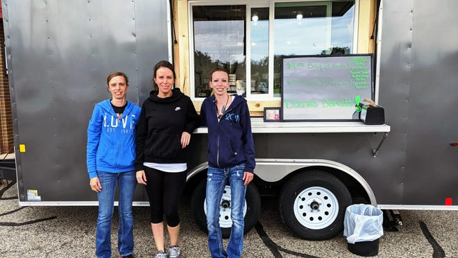 Three sisters pose for a photo outside Donna's Donuts -- a food trailer named for their late mother.